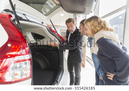 Car dealer showing vehicle binnacle to clients - stock photo
