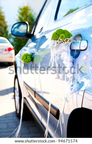 car decorated for wedding - green bouquets, shallow depth of field - stock photo