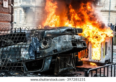 car destroyed and set on fire during the riots. city center - stock photo