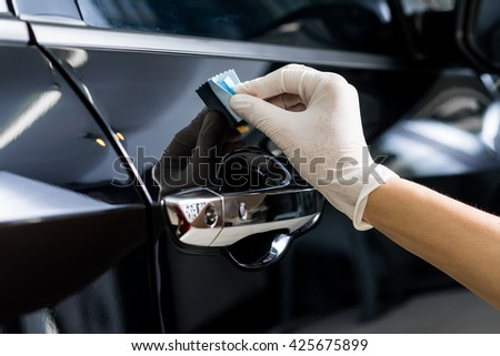 Car detailing series : Closeup of hand polishing black car door