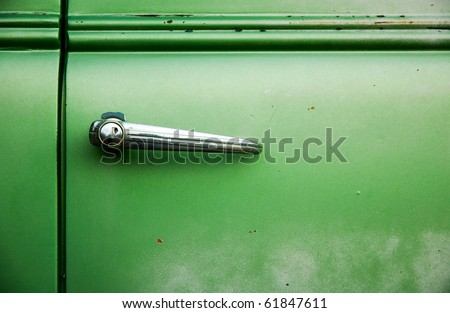 Car door handle on a green door.