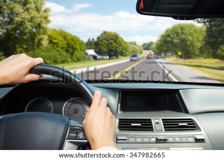Car driver hands. People driving on driveway. - stock photo