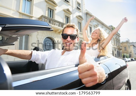 Car driver happy giving thumbs up - driving couple excited on road trip travel vacation. Male driver wearing sunglasses. Lifestyle with beautiful cheerful lovers, man and woman. - stock photo