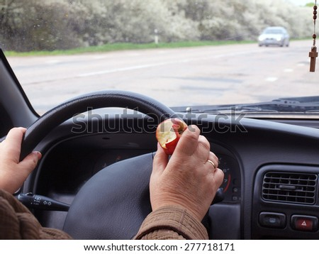 Car driver holding an apple near steering wheel