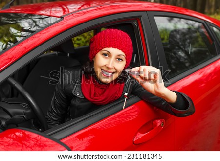 Car driver in red car showing keys. - stock photo