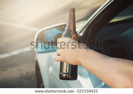 Car driver is holding a bottle of beer in his hand - stock photo