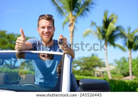Car driver showing keys and thumbs up happy. Young man holding car key for new leasing convertible. Rental cars or drivers licence concept with male driving cabriolet on road trip. - stock photo