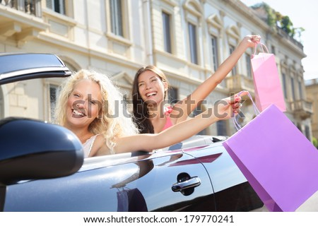 Car driver woman driving and shopping with girl friends holding shopping bags happy and excited on road trip travel vacation in convertible car in summer. Two beautiful women girlfriends shoppers.
