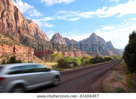 Car drives at high speed along highway through scenic Zion National Park with colorful sandstone and shale mountains and rock formations
