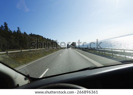 car driving a scenic highway route, seen from drivers perspective, vantage point. - stock photo