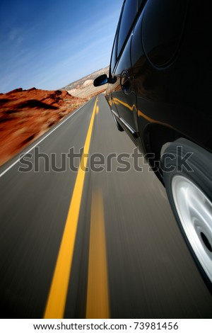 Car driving down rural road in Wyoming. Focus on mirror. Mounted camera, natural motion blur. - stock photo