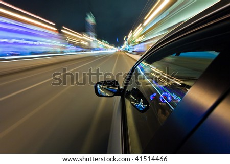Car driving fast in the night city - stock photo