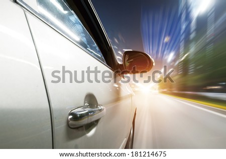 Car driving fast into a city - stock photo