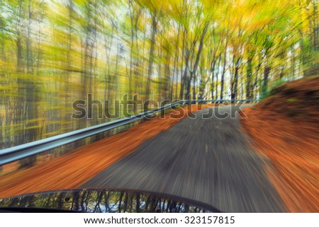 Car driving fast into autumn forest - stock photo