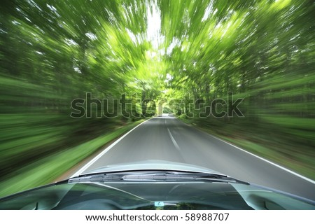 car driving fast into forest - stock photo