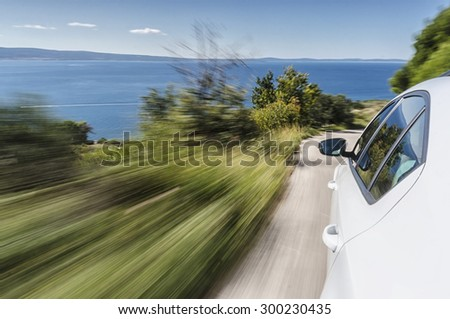 Car driving fast on a mountain road towards the sea - stock photo
