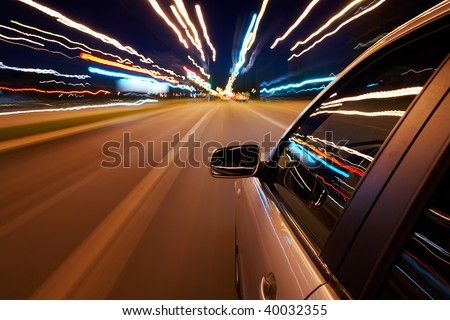 Car driving fast on a night city road - stock photo