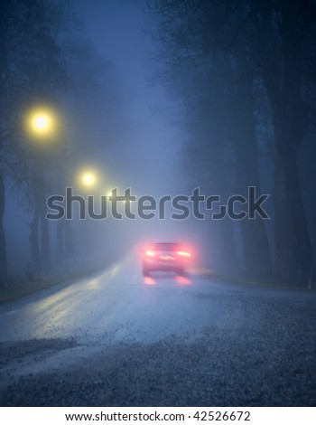 Car driving in a dark avenue in thick fog - stock photo