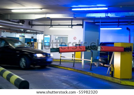 car driving in a parking garage with blue light - stock photo
