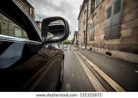 Car driving in old European town in France. - stock photo