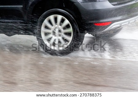 car driving in the rain on a wet road. danger of aqua planning and accidents - stock photo