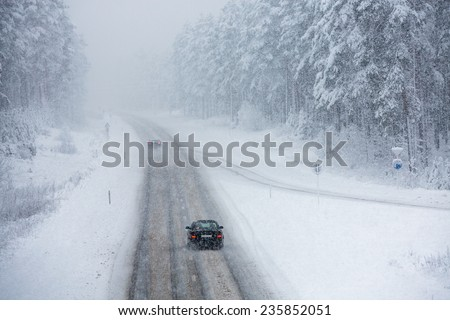 Car driving on snow road - stock photo