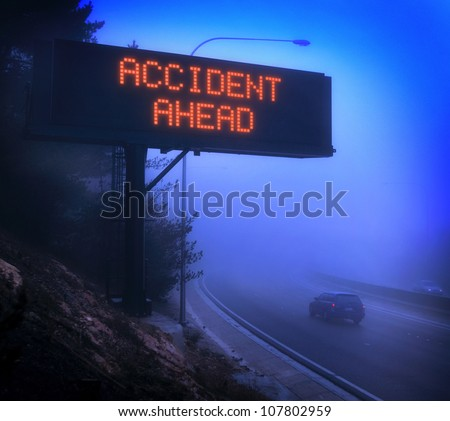 Car driving sown a foggy highway with a warning sign showing Accident
