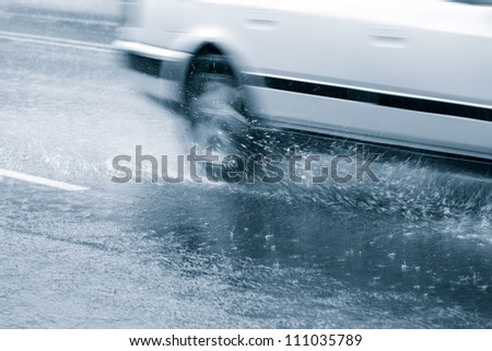 Car driving through in a downpour