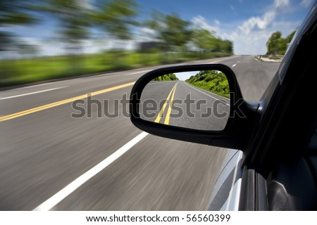 car driving through the empty road and focus on mirror - stock photo