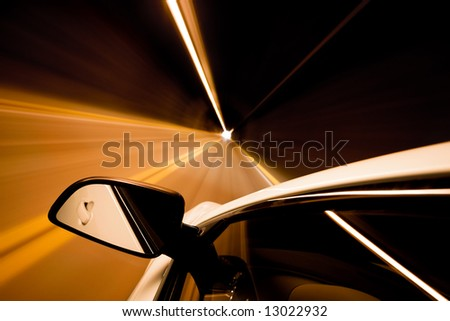 car driving through tunnel with motion blur, focus on mirror - stock photo