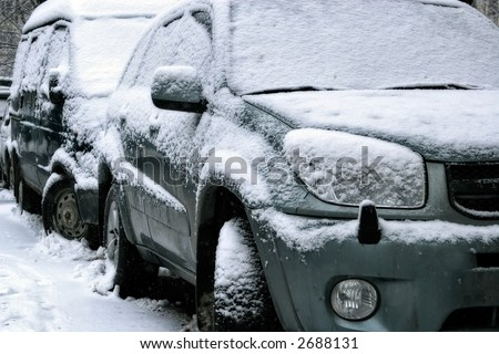 Car during a snowfall in town-snowdrift in city creates greater problems for automobile movement - stock photo