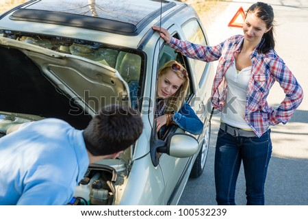 Car failure man help two female friends repair motor - stock photo