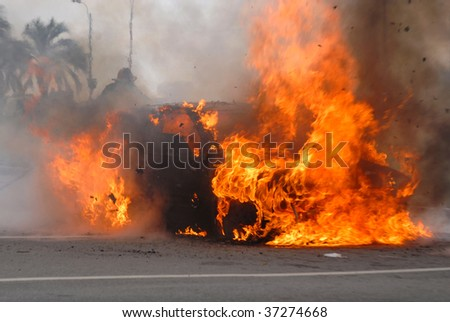 Car fire and firefighter trying to extinguish the flames