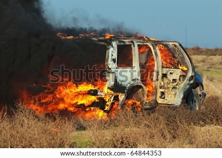 Car fire on desert rural road - stock photo