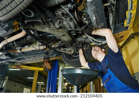 car garage auto mechanic repairman tighten screw with spanner during automobile maintenance at repair service station - stock photo