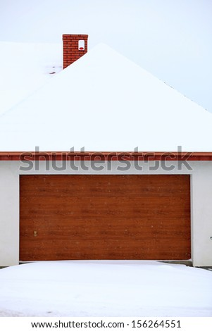 car garage door surrounded by snow, winter time - stock photo