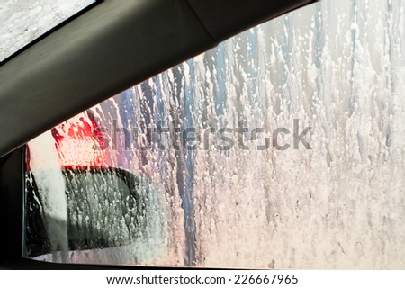 Car getting a wash with soap, view from inside - stock photo