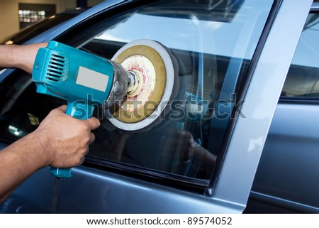 Car Glass polishing with power buffer machine. CAR CARE images. closeup Useful as background for design-works. - stock photo