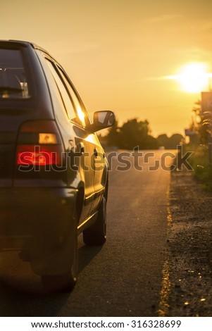 Car going toward sunset through countryside - stock photo