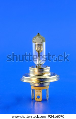 Car halogen bulb stands in the foreground against a blue background