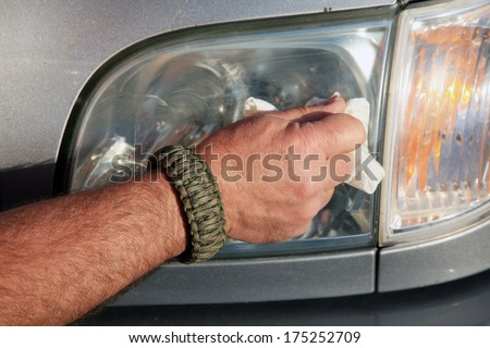 Car Head Light Repair de-fogging of plastic Head Light Covers by hand with a paper towel and a special Rejuvenation Cream made especially to fix fogged Head Lights. Now I can drive at night again  - stock photo