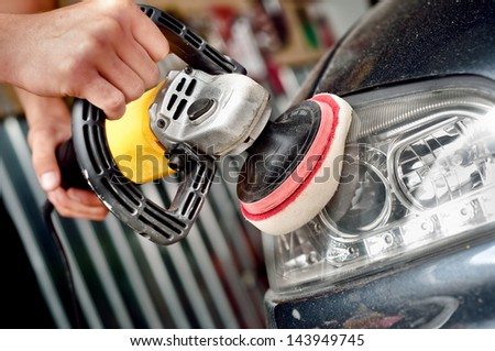 Car headlight cleaning with power buffer machine at service station - stock photo