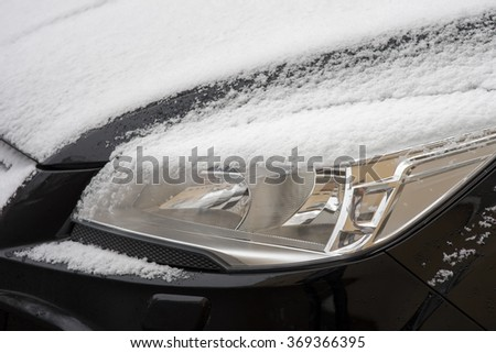 car headlights covered in snow in winter / Winter time - stock photo