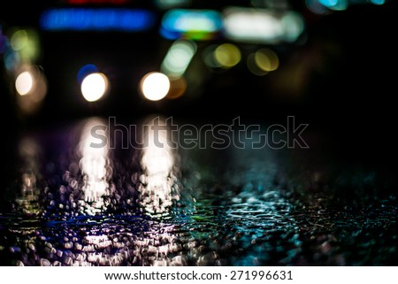 Car headlights shine at night. View from the level of asphalt - stock photo