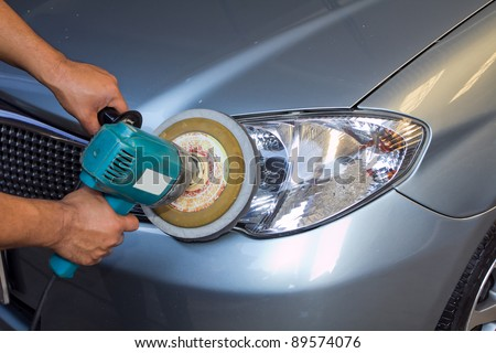 Car headlights with power buffer machine at service station - a series of CAR CARE images. - stock photo