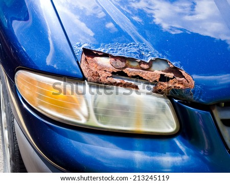 Car Hood with a Hole from Rust and Corrosion - stock photo