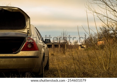 car in a field on a background of derelict buildings - stock photo