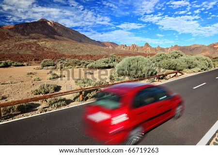 Car in beautiful landscape. Red car road trip image from Tenerife, Canary Islands. Volcano Teide in the background.