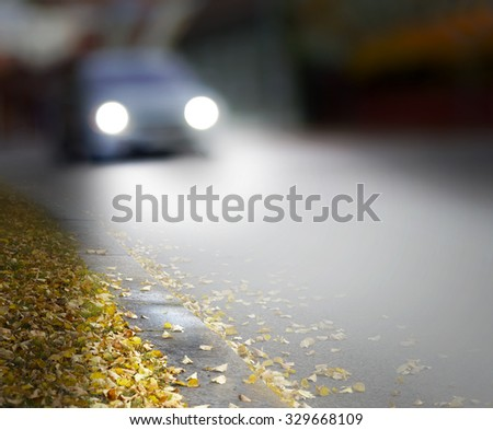 car in blurred motion in city street with switched on headlights in autumn - stock photo