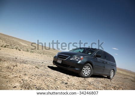 Car in desert under blue sky - stock photo